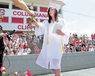 Lauren Houck walks across the stage to get a red rose after being handed her diploma during Columbiana High School's graduation program at Harvey S. FIrestone Park on Sunday. The seniors were later asked to present their flowers to a loved one in the audience who the felt helped them the most to succeed. A total of 66 students received their diplomas.