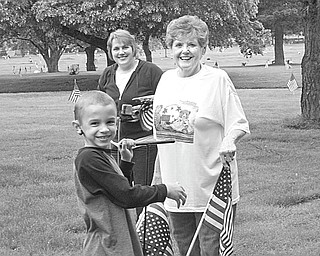 Above, Lukas Peters, a member of Cub Scout Troop 114, helps place flags on graves at Calvary Cemetery along with Jeannie Kettler, right, of VFW Post 93, and his mother, Chris Peters, who serves as den mother for the troop. Below, some members of Girl Scout Troop 977 were presented with certificates by Robert Dutton, commander of VFW Post 93 in recognition of their assistance in flag-decorating at the cemetery.