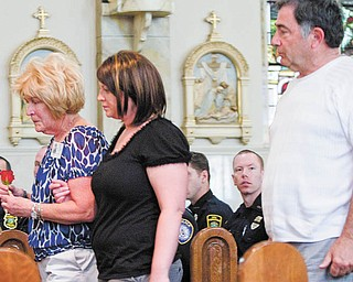 Mary Kay Hartzell of Austintown carries a rose to place at a memorial service honoring Mahoning CountyÕs police offi cers who died in the line of duty. HartzellÕs son, Michael T. Hartzell, a Youngstown police offi cer, was shot and killed April 29, 2003. She is escorted Thursday inside Our Lady of Mount Carmel Church, Youngstown, by Stephanie Harchar, a county deputy sheriff and HartzellÕs fi ancŽe. Behind them is HartzellÕs father, Howard. Twenty-four offi cers have died in service since 1891.