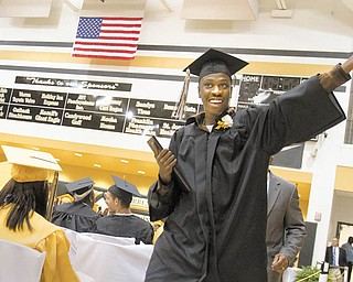 Darien Young motions for applause after he accepts his diploma during Warren G. Harding High School's 2010 commencement ceremony Wednesday.