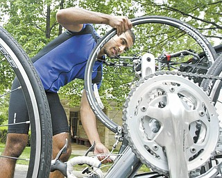 Jose Medina, co-director of 4K for Cancer, checks his bike at Westminster Presbyterian Church in Boardman on Thursday after riding from Butler, Pa. 4K for Cancer, a nonprofit group of 28 bicyclists, is traveling 4,000 miles, starting in Baltimore earlier this week and ending July 31 in San Francisco.