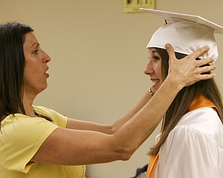 ROBERT K. YOSAY | THE VINDICATOR..Putting her cap on straight  Lauren DiCola gets an assist from Mrs Craig Yardas  before graduation exercises at Boardman High Schools Graduation 2010 held at the school -30