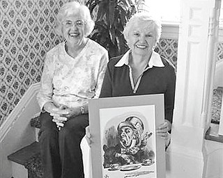 """Amused by one of the pictures to be used as a decoration during the """"Alice in Wonderland"""" tea and garden tour planned by Columbiana Women's club, are above, from left, Marian Hutson and Helen Gormley, who will be in charge of the """"Mad Hatter"""" accessory sale at the event."""