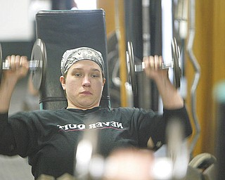 Chelsi Figley grimaces as she practices the bench press. The 27-year-old East Palestine resident, who is afflicted with spina bifida, will compete in the Paralympic Games in Malaysia later this year.