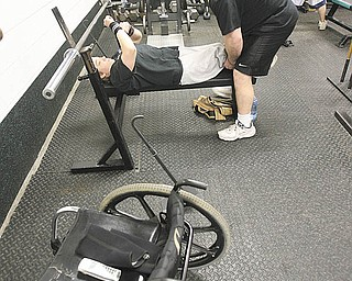 Chelsi Figley's personal trainer Brian Raneri does more than provide workout motivation. He also helps the Paralympian weightlifter move from her wheelchair into position on the bench.