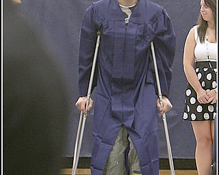 ROBERT K. YOSAY | THE VINDICATOR..putting his best foot forward at graduation .. even if its in a cast is Kyle Gump as he makes his way to his seat at Lowellville High School gym - the glass of 2010 - graduated Sunday afternoon-30