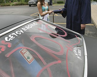 ROBERT K. YOSAY | THE VINDICATOR...Almost ready as Jeff Getsy picks up his graduation cap held by Amanda Pesta ( girlfreind) - Getsy came with 2010 written o his racing 77 Vega. at Lowellville High School gym - the glass of 2010 - graduated Sunday afternoon-30