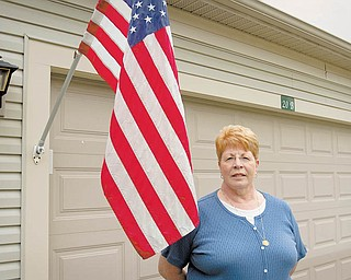 Karyn Frederick stands alongside an American flag that she flies every day of the year outside her Canfield home. It is a tradition instilled by her father, a World War II veteran. She says she is saddened that many Americans no longer hold great reverence toward the flag.