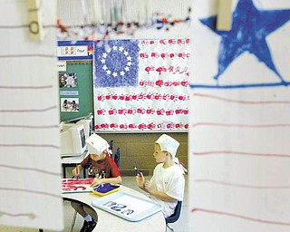 Aidan Frease, left, and Michael Vukovich, both 7 and participants at Sunny Days Child Care Center in Girard, work on a Flag Day project.