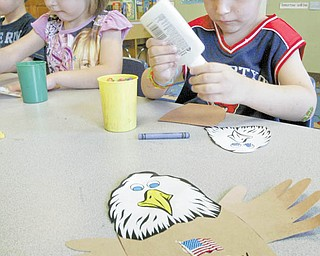 4-year-olds Faith Sullivan and Nicholas Ricottilli concentrate on gluing wings on a bald eagle, the emblem of the United States, as part of a Flag Day craft project at Lads 'N Lassies Academy in Boardman.