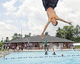 Lamar Robinson, 13, of Youngstown does a flip from the diving board at North Side Pool shortly after the pool opened Wednesday. The opening was made possible thanks to funding through the Mahoning-Youngstown Community Action Partnership.