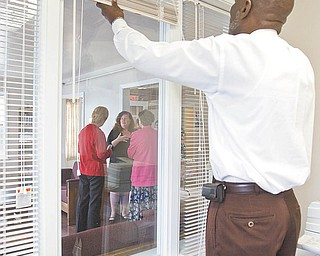 Edward Neil Bunkley, program coordinator for Daybreak Youth Crisis Shelter, adjusts the blinds in his new office, part of the addition to the facility for runaway and homeless children. From his office, Bunkley can observe residents in the living room. A grand opening for the shelter was Thursday.