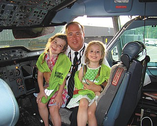 "Todd Tobey of Boardman, who is an airline pilot, and his daughters, Madelyn and Natalie, are sitting in the cockpit of an Airbus A-300 jumbo jet on ""Take Your Daughters to Work Day."""