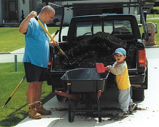 Tony Cougras of Poland is a good sport about the mulch that didn't make it into the wheelbarrow when he was  getting a helping hand from his son, Michael.
