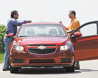In this photo made June 9, 2010, General Motors engineers Wayne McConnell, left, director of vehicle performance integration and Brandon Vivian, performance manager for the Chevrolet Cruze confer during a road test of a pre-production model in Milford, Mich. With the Chevrolet Cruze, General Motors is on the verge of building its first decent small car. Yet it won't be easy for the automaker to win over a skeptical America. People know that Nothing Works Like a Chevy Truck, but are they willing to gamble on a company with a long history of small-car disasters. (AP Photo/Paul Sancya)