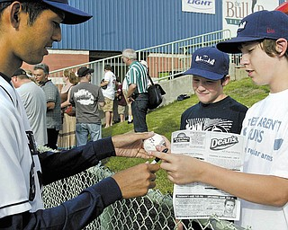 Before the start of Monday's home-opener game at Eastwood Field in Niles, Mahoning Valley Scrappers player Takafumi Nakamura, left, signs a baseball ball for fans Joe Homa, 11, center, and Tyler Longwell, 13, both of Warren. The Scrappers opened their 11th season as a Minor League affi liate of the Cleveland Indians.