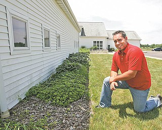 Justin Rogers, Mill Creek MetroParks landscape architect, kneels where a $10,850 educational rain garden will be installed at the MetroParks Farm in Canfield. The MetroParks was one of 19 applicants to receive a surface-water-improvement grant through the Ohio Environmental Protection Agency.