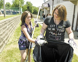 Karah Roby, 16, left, and Mary Vanjura, 15, Campbell students involved in Bright Futures at Westminster College, clean up outside Neighborhood Ministries on Jackson Street. The girls were participating in community-service projects Monday with 34 other Bright Futures students.