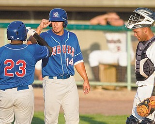 Mahoning Valley Scrappers catcher Moises Montero looks down as Lance Durham (23) and John Roberts (14) of the Auburn Doubledays celebrate after scoring in Tuesday's game at Eastwood Field in Niles. The Doubledays shut out the Scrappers, 5-0, for their second time in a row.