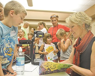Michael Hvizdos, 7, of North Lima gets an autograph Wednesday from childrenÕs author and illustrator Cyd Moore at the Boardman Library. Moore spoke about her life and artwork to kick off the public libraryÕs summer reading program..