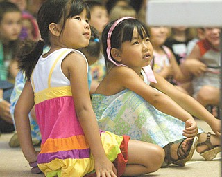 Best friends Emily Choleva, 5, and Kira Vasko, 5, both of Boardman, sit rapt with attention at the summer program at the Boardman Library.