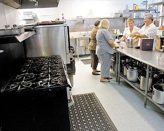 Volunteers prepare refreshments in the newly remodeled kitchen at the St. Vincent De Paul Society Dining Hall. The facility, which serves meals to people in need, just completed a renovation.