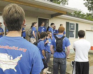Monica Craven, far right, executive director of Mahoning County Habitat for Humanity, gives instructions to a group of 30 cyclists from Bike & Build, a nonprofit organization that helps build affordable housing as it travels a cycling route. The group pitched in at a Habitat house on Maranatha Drive in Youngstown.