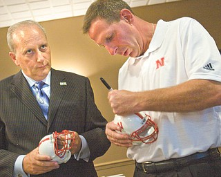 """Bob Hannon, left, president and chief professional offi cer of the United Way of Youngstown and the Mahoning Valley, watches as University of Nebraska football coach Bo Pelini autographs miniature football helmets during the organization's """"Champions Among Us"""" banquet Tuesday at Antone's Banquet Centre in Boardman. Pelini, a graduate of Cardinal Mooney High School and The Ohio State University, spoke about how pride in his roots molded him into a successful coach."""