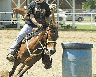 Mariah McGeehen, 13, of Newton Falls, is a picture of concentration as she guides her horse, Starr, around a barrel in preparation for 4-H competition at the Trumbull County Fair. Fair officials said the number of 4-H participants is up for this year's events.