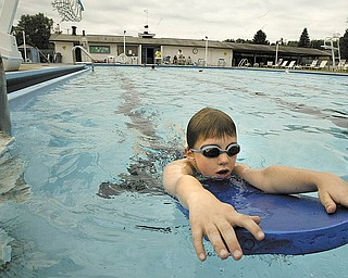 Andrew Garr, 9, of Boardman uses a fl otation board as he enjoys the pool at Logan Swim & Tennis Club in Liberty. The club is promoting a membership drive in July for the facility that offers a swimming pool with two one-meter diving boards, competitive starting blocks and shallow and deep ends. There also are tennis and basketball courts.