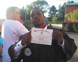 Reginald Jermaine Isiah Ware shows off his diploma following graduation from Campbell Memorial High School.