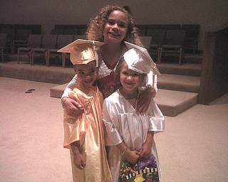 Big sister Delia Walkowiec, 9, congratulates brother Zenin, and classmate Maria Slaton, 5, of Austintown at preschool graduation from For Kids Sake.