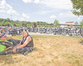 Gary Mathews of Ellsworth, a member of the Blue Knights of Ohio, and Patty Cleburn of Columbiana relax on the grass as they await the start of the eighth annual memorial motorcycle run. The Blue Knights co-sponsored the run.