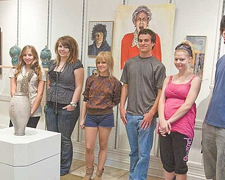Artists, left to right, Nikki Mehle of Canfield, Hailey Snow of Youngstown, Valerie Nichols of Austintown, Ben Belgrad of Boardman, Jessica Grizinski of Boardman and Justin Reese of Youngstown stand with their artwork displayed at the Art Outreach Gallery.