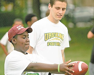 Matthew Taylor 12, of Austintown gets some pointers from the class of 2008 kicke Michael Metzinger at the Ursuline High School Footbal Camp.