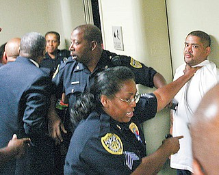 Youngstown police use force to break up a melee Wednesday morning in the hallway of the Youngstown Municipal Court in City Hall. The fight began between the friends and family members of murder suspect Melvin Shaw and those of shooting victim Tracee Banks. Shaw was arraigned before the melee.