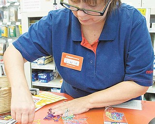 CVS employee Valarie Dodge, shows the different Silly Bandz shapes that are made of silicone and die molded. The rubber bands return to their original shape when you take them off.