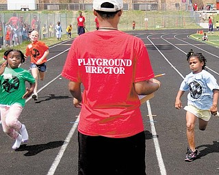 Under the watchful eye of a playground director, Leah Harris, 6, left, and Jalaya Brown, right, both of Youngstown, race to the finish line in the 50-meter dash at the Youngstown Park and Recreation Department's annual track and field day at Cardinal Mooney High School. Behind Leah is Ana'Lyse Cole, 7, of Struthers. The unidentified director recorded the order of finish Thursday.