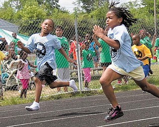 Kevon Weaver, 7, left, of Youngstown, goes shoeless in his race with Jalaya in the 50-meter dash. The children in the park department's summer day-camp program were able compete in various track and field events.