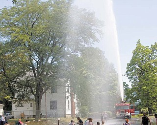 Above left, a firetruck from Youngstown Fire Station 2 provides a water spray for participants in the summer camp Thursday at Martin Luther Lutheran Church, 420 Clearmount Drive, Youngstown. Among activities this week for the children age 6 to 15 were Bible stories, music and crafts.