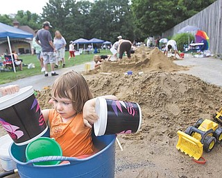 Sophia Danchise, 2, of Youngstown takes a break from sand sculpting to play in a bucket during Sunfest in Mill Creek Park on Sunday.