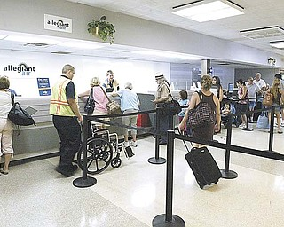 Passengers wait to check in at the Youngstown Warren Regional Airport. A market survey points out that the top six flight destinations for Mahoning Valley residents are in tourist areas Ñ Orlando, Las Vegas, Tampa, Fort Lauderdale, Fort Myers, and Nashville..