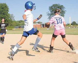 Abby Masluk, center, makes her way to fi rst base, as Maddie Rowe, left, throws to Aleah Hughes during Poland's 11-12 Little League softball practice on Tuesday.