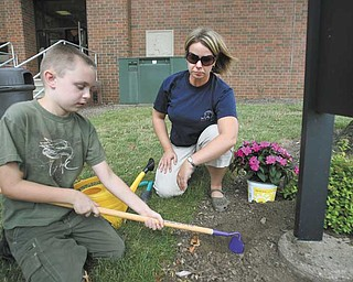 Zachary Donatella, 9, of Poland, works the ground under the guidance of teacher Vanessa Sabo outside the Rich Center for Autism. Children in the program spent time this summer in the Outdoor Healing Garden in front of Fedor Hall, Youngstown State University.
