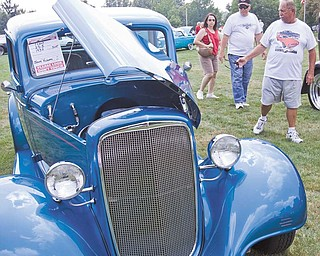 Marlene and Larry Clark of Canfield and Jim Bradick of Youngstown, check out Jerry Kolesar's 1935 Chevy at Boardman Park for the Mahoning Valley Olde Car Club car show.