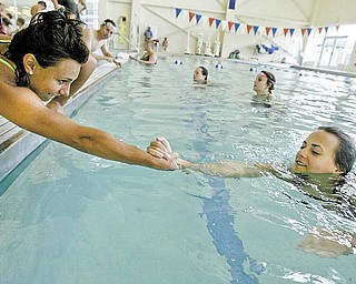 Carle Tofil, 16, left, of Struthers and Margo Ucchino, 18, of Poland practice rescue techniques during a lifeguard-training class at the D.D. & Velma Davis YMCA in Boardman.