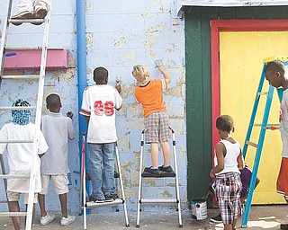 Young neighborhood volunteers scrape chipped paint and brush on fresh paint to the side of the former Sparkle Market at 2410 Glenwood Ave., Youngstown. James London, president of Idora Neighborhood Association, said the group received a $2,000 grant from the Wean Foundation for this project. He credits his granddaughter, Sierra Hopson, 6, for the mural drawing. The effort also included volunteers from Art Youngstown Inc. and Goodness Grows.