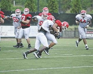 Defender Brandian Ross, left, tackles Jamaine Cook during a recent Youngstown State University scrimmage. Ross is one of the Penguins' team captains for 2010.