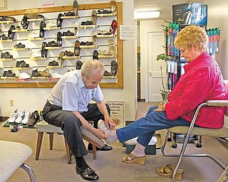 Joe Marzano, of Youngstown's South Side, helps Myra McClain, of Canfield, try on a pair of shoes at Diorio Shoes in Poland on Wednesday afternoon.