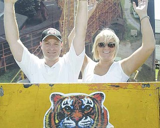 George Summers and Melanie Smith pose in a Wildcat roller-coaster car from Idora Park on display at the Canfield Fair. Smith's father, Robert Karzmer of Youngstown, found the 1,000-pound original coaster car in a local body shop.